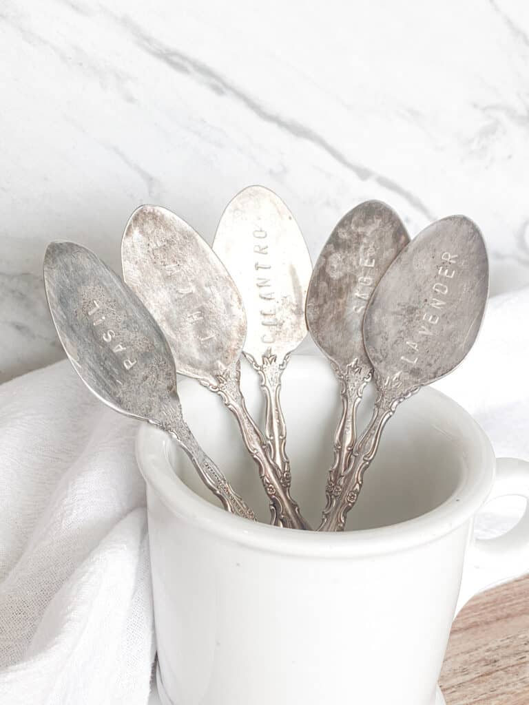 antique stamped spoons in a white ironstone mug in front of a marble backpslash