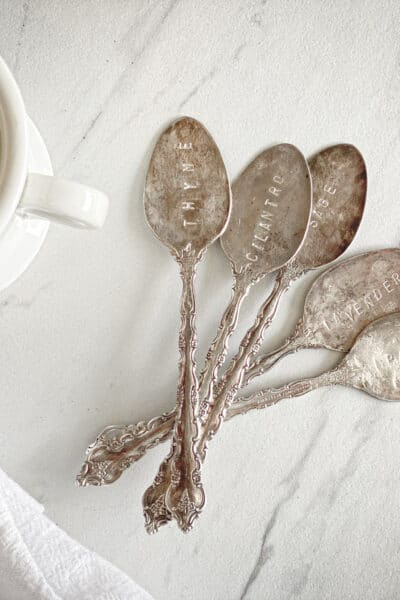 stamped antique spoons next to ironstone mug, flour sack towel and marble