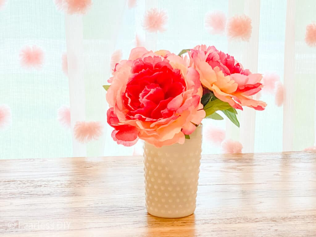 pink peonies in a white hobnail jar on a wooden childs table in front of shear curtains with pink puffballs staged by fearlessdiy.com