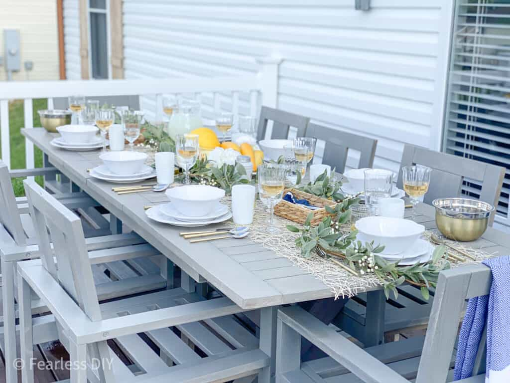 Pottery Barn Outdoor Table set with ivory dishes, crystal glassware, gold utensils with a centerpiece of lamb's ear with yellow melons, squash and candles style by fearlessdiy
