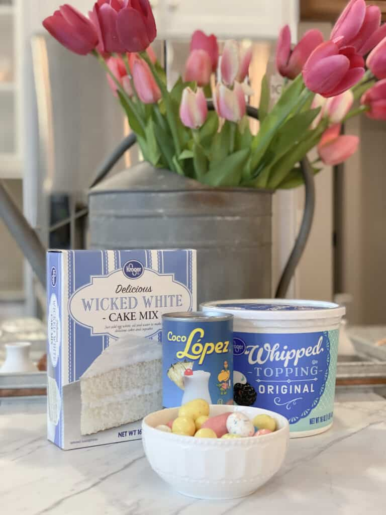 Boxed cake mix, cream of coconut, tub of whipped topping and Robin's Egg candy in front of a galvanized watering can filled with pink tulips