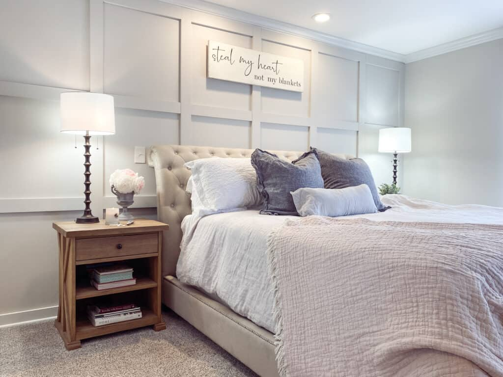 board and batten master bedroom with linen bedding, natural wood nightstand