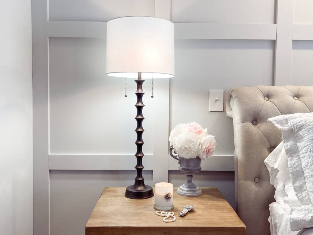 board and batten master bedroom wall with black lamp on natural wood nightstand with a string of pearls, watch and candle