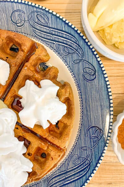pumpkin spice waffles with syrup and whipped cream