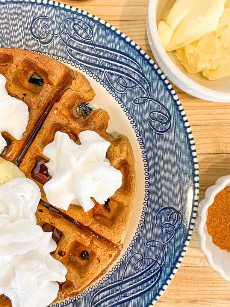 pumpkin spice waffle with syrup butter and whipped topping