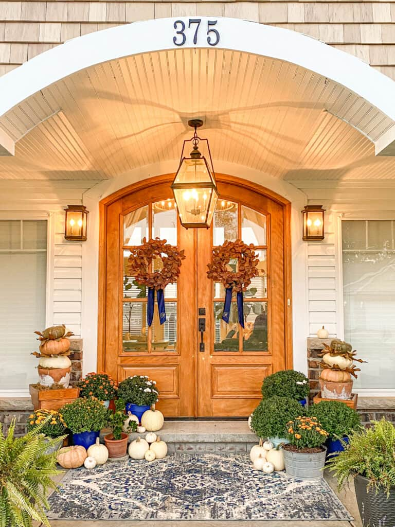 arched wooden double front doors with fall wreaths with blue velvet wreath sashes. The door is framed by mums, white, orange and green pumpkins.