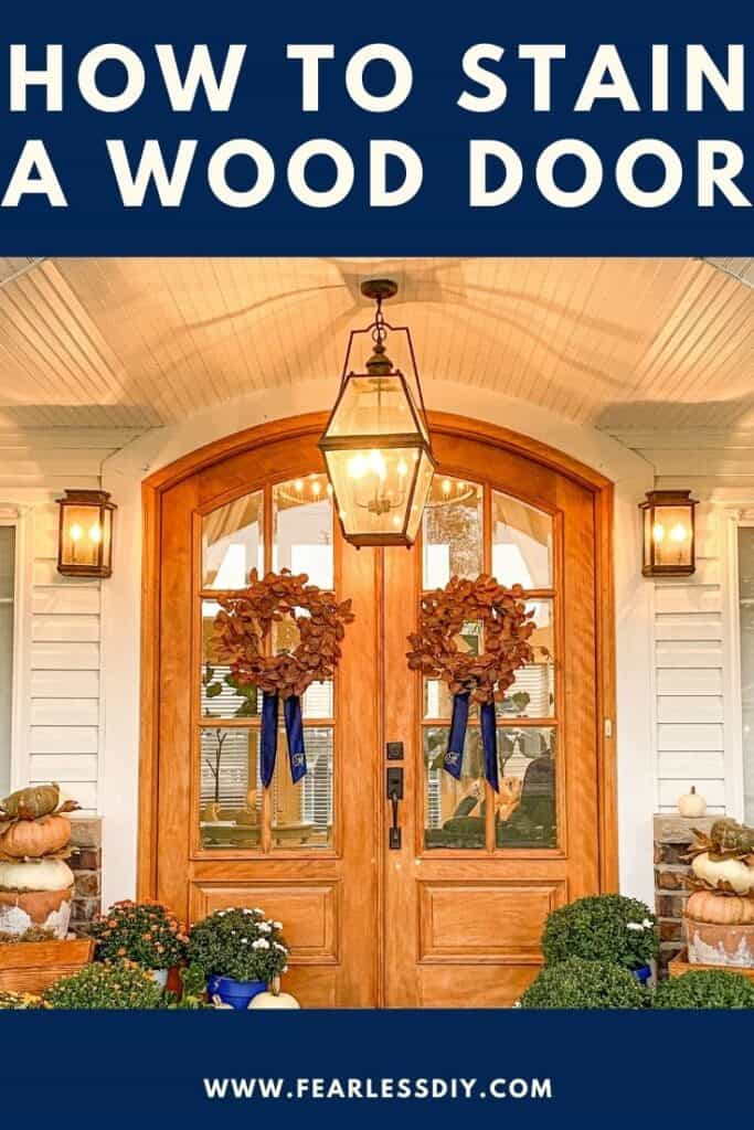 Arched wooden front doors with rust eucalyptus wreaths with blue velvet wreath sashes.
